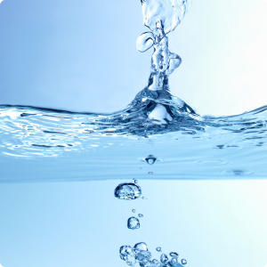 A drop of water plunges into a body of water creating a ripple effect.